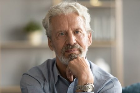 Portrait of thoughtful pondering middle aged hoary man touching chin, looking at camera. Head shot close up pensive mature old grandfather thinking of problems difficulties, retirement life concept.